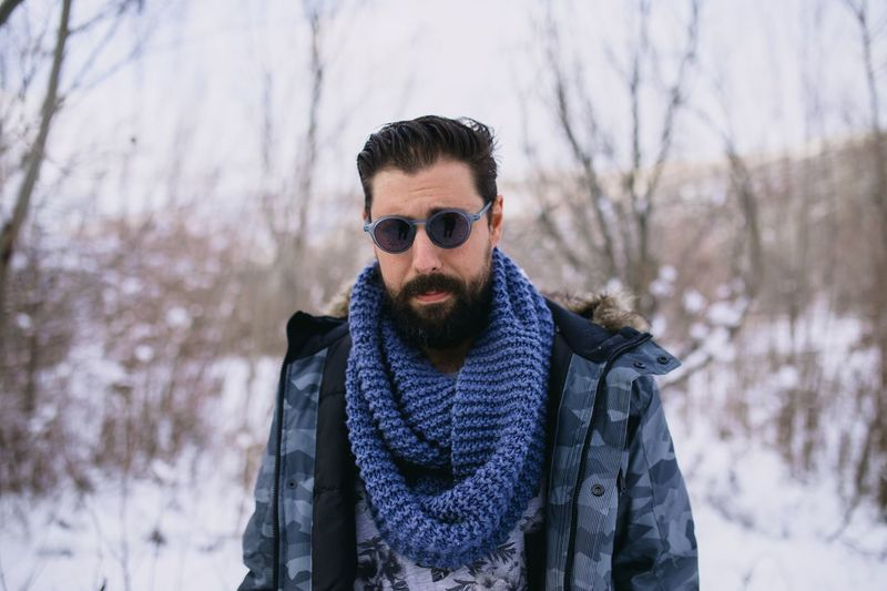 Portrait of man wearing sunglasses standing in forest during winter
