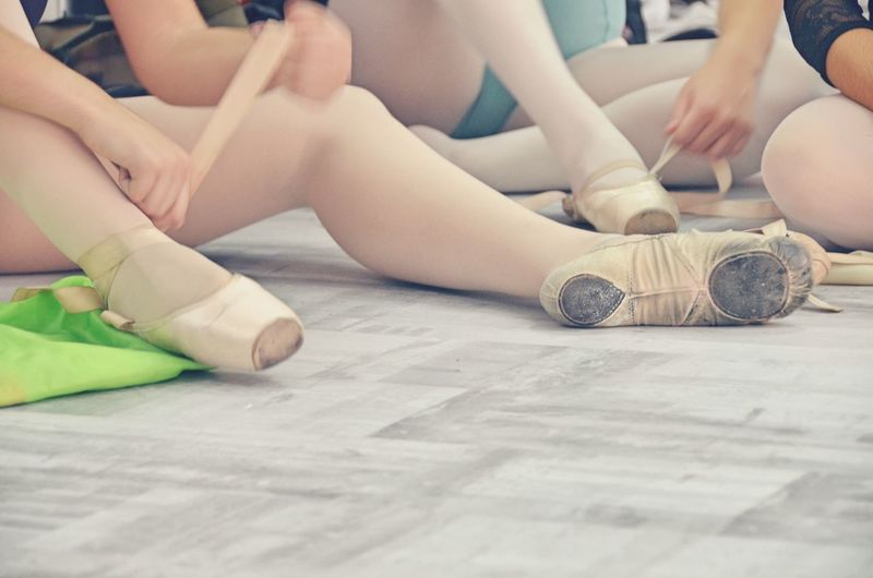 Low Section Of Women Wearing Ballet Shoe At Studio