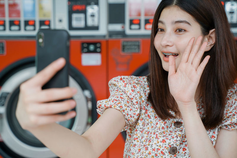 Portrait of a smiling young woman using mobile phone