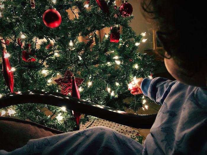 Man sitting on illuminated christmas tree at home