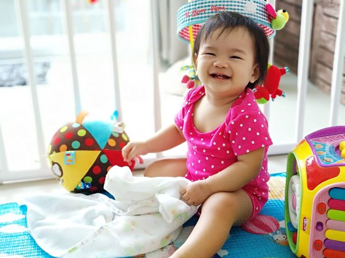 Portrait Of Cute Baby Girl Sitting By Toys On Bed At Home