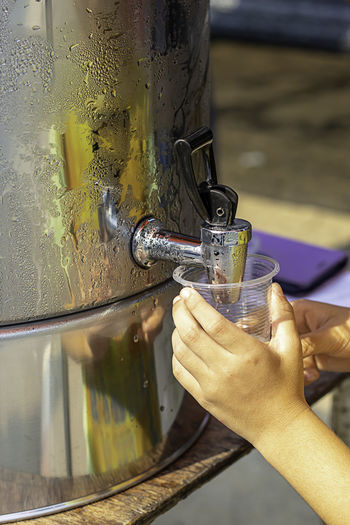 Cropped image of child filling water in plastic cup from faucet