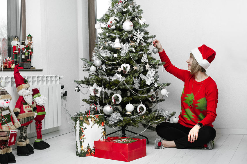 Decoration Decorations Smiling Smile One Person Women One Woman Only One Young Woman Only Young Women People Real People Christmas Decoration Christmas Present Gift Tree Christmas Winter Celebration Holiday - Event Red Reindeer Santa Claus Christmas Ornament Bauble Arms Raised christmas tree December Christmas Bauble Human Arm Decorating The Christmas Tree