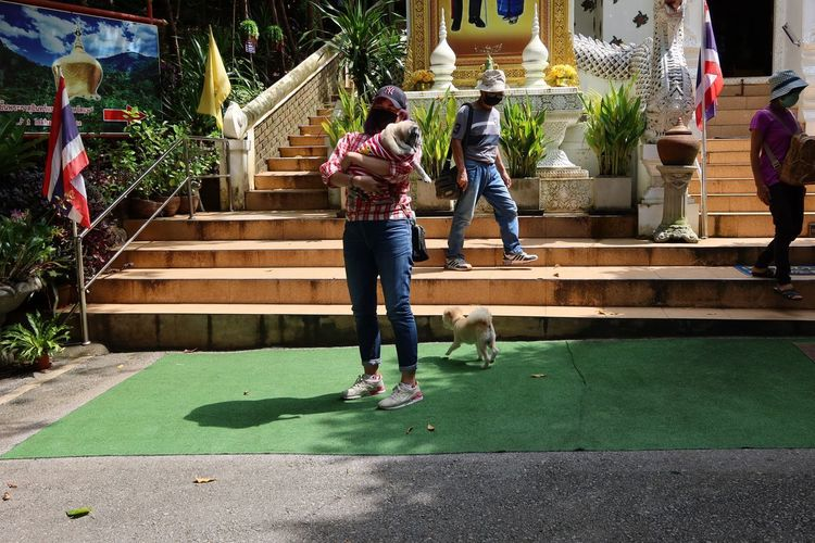 Rear view of woman with dog walking on staircase