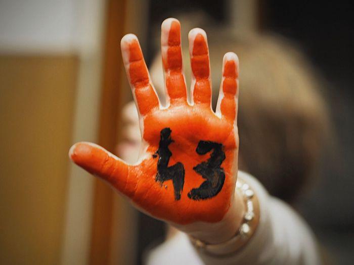 Close-up of hand holding orange pumpkin