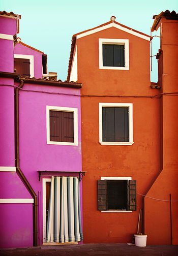 two houses painted in striking colors in Burano, small island near Venice Architecture Building Exterior Built Structure Burano Island Day Facades Fisher Village Home Italy No People Orange Outdoors Painted Houses Pink Rustic Charm Shutter Stricking Colors Venetian Lagoon Vibrant Colors Violet Window