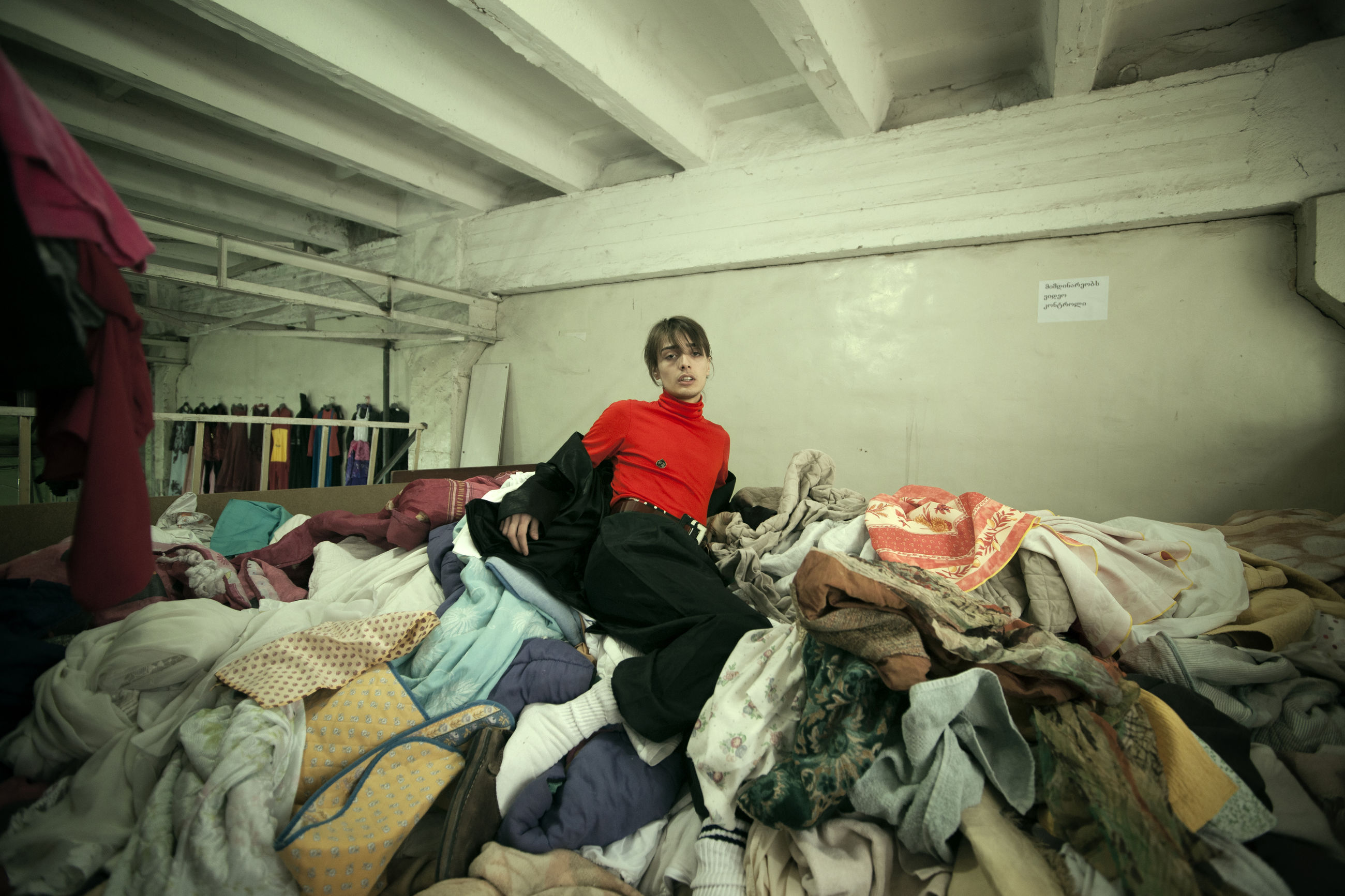one person, real people, indoors, looking at camera, clothing, portrait, furniture, front view, women, stack, occupation, large group of objects, architecture, lifestyles, domestic room, adult, sitting, young adult, young women, messy