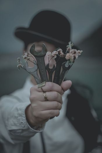 Woman holding wrenches and flowers