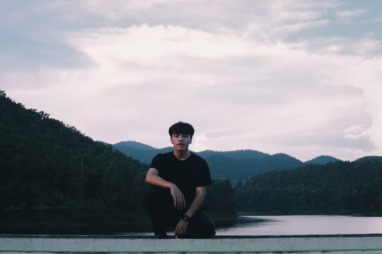 Portrait of young man sitting on mountain against sky