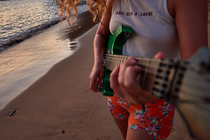 Midsection of woman playing guitar at beach