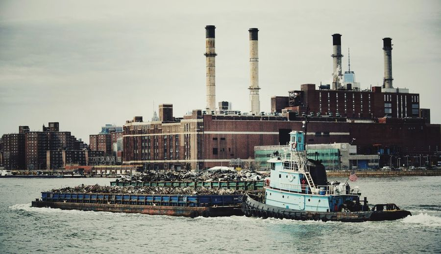 Tugboat Pulling Barge Against Buildings