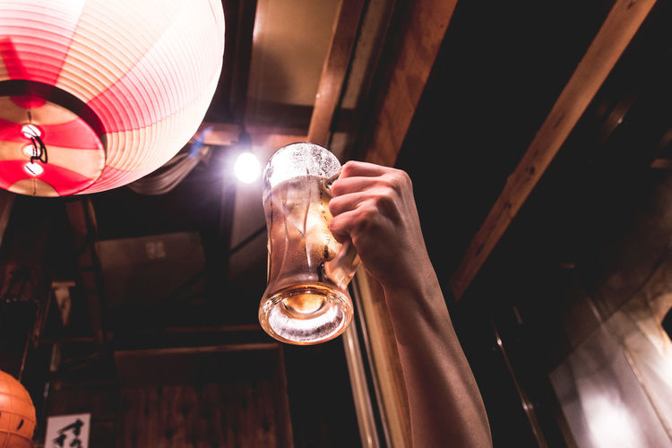 Cropped Hand Holding Beer Glass By Lantern
