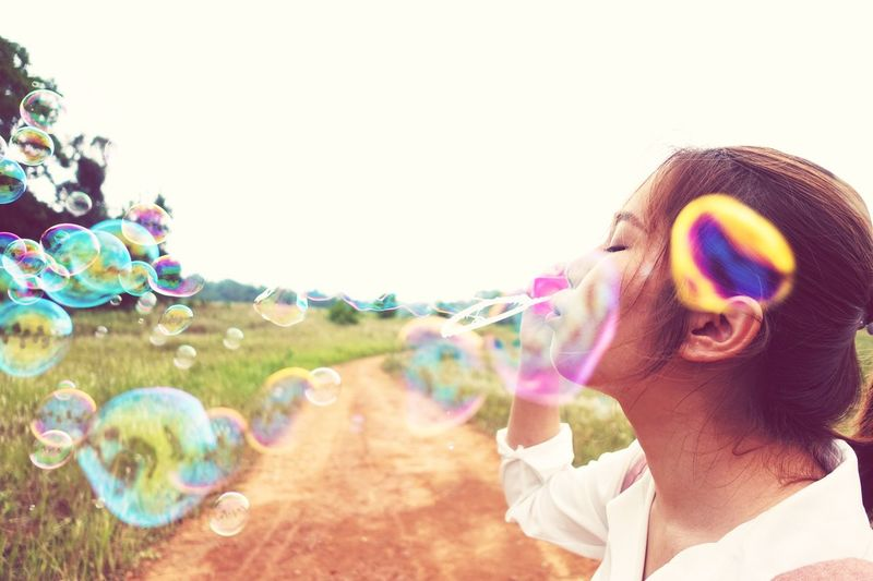 Lifestyles Fun Field Dreaming Dream Colorful Bubble Headshot Blowing Leisure Activity Portrait Nature Lifestyles Day Happiness Outdoors Adult Young Adult One Person