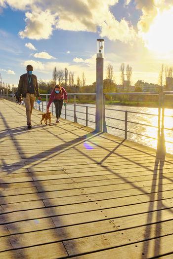 Rear view of people walking on water against sky