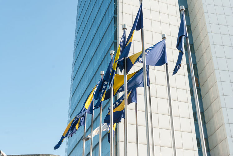 Low angle view of bosnia and herzegovinan flags and modern building against clear blue sky