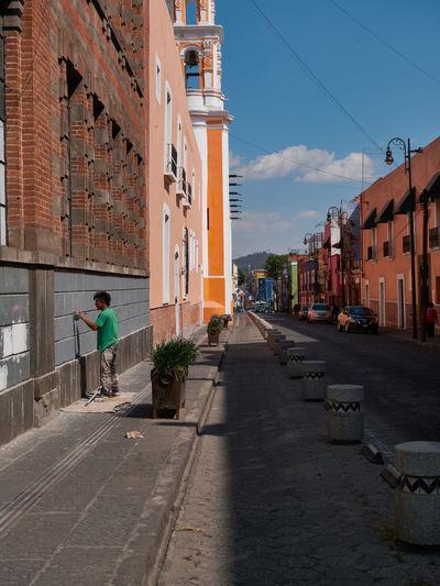 Man walking on footpath amidst buildings in city