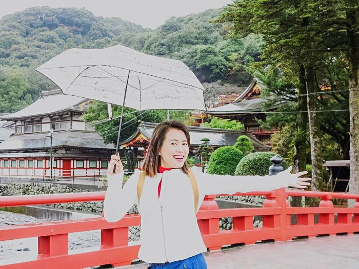 Portrait of happy woman with umbrella against traditional buildings