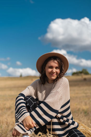Portrait of smiling young woman on field against sky