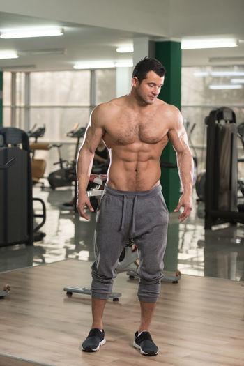 Full length of shirtless man standing in illuminated room