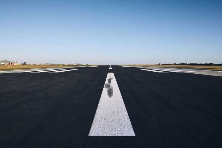 Airport runway against clear sky
