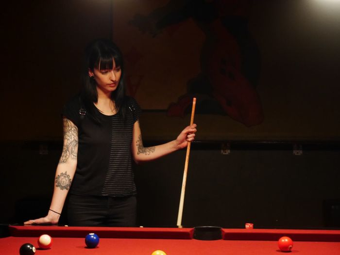 Young woman standing by pool table