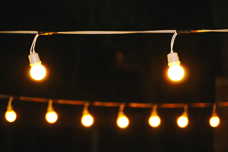 Low angle view of illuminated light bulbs hanging at night