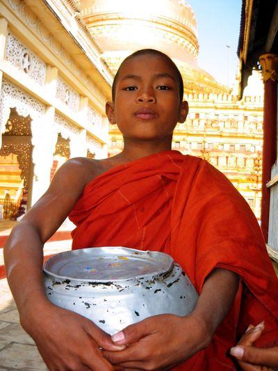 Novice monk holding alms bowl, Shwezigon Pagoda, Bagan Myanmar Buddhist Shaved Head Alms Bowl Boy Front View Looking At Camera Novice Monk Orange Robes Portrait Shwezigon Pagoda