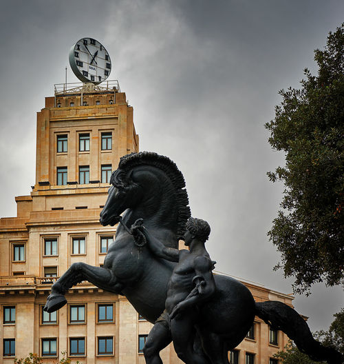 Low Angle View Of Horse And Man Statue Against Clock Tower At Placa De Catalunya