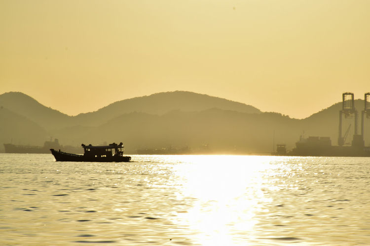 Silhouette boat in sea against clear sky during sunset