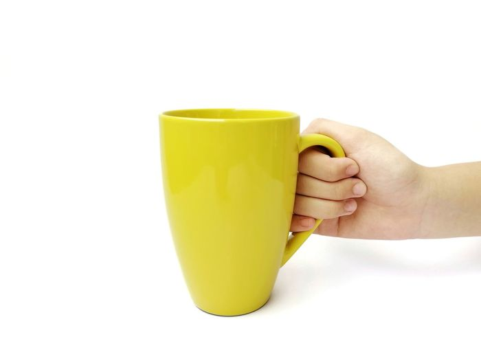 Close-up of hand holding yellow against white background