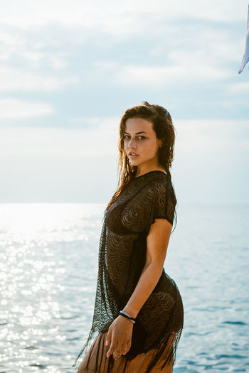 Portrait of young woman standing by sea against sky
