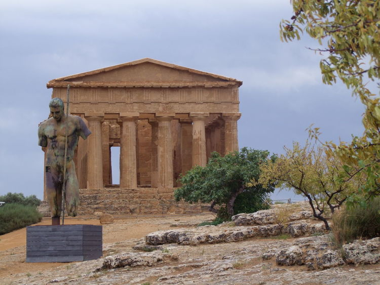 Doric Temple of Concord (5th century) & Bronze Statue Agrigento Ancient Ancient Civilization Architecture Blue Sky White Clouds Bronze Building Exterior Built Structure Column Composition Day Exterior Famous Place Historic History International Landmark Italy No People Roman Ruined Sculpture Sicily The Past Tourist Attraction  Trees