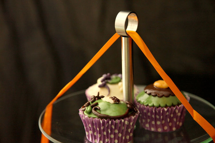 Close-up of halloween cupcakes on cakestand against black background