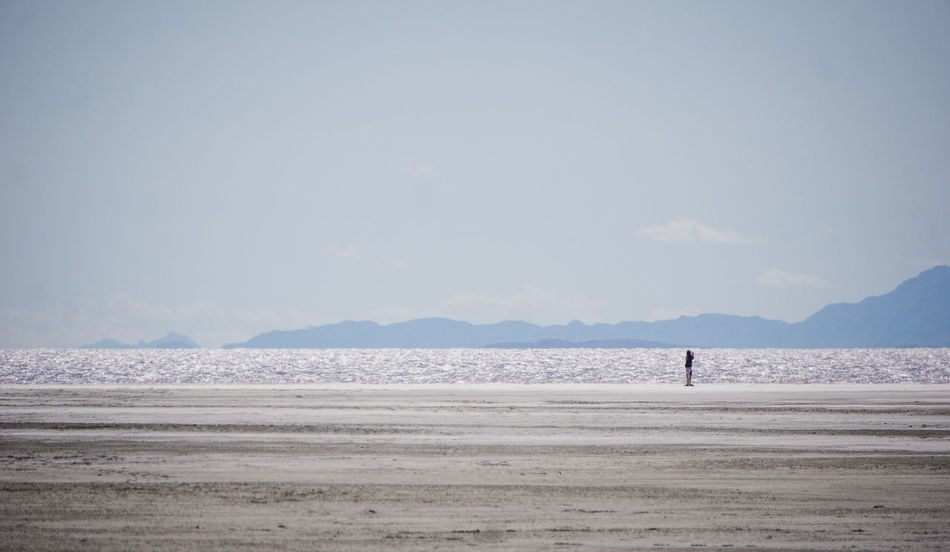 exploring the shore of the Great Salt Lake near Spiral Jetty. Beauty In Nature Coastline Day Great Salt Lake Idyllic Leisure Activity Lifestyles Mountain Nature Non-urban Scene Outdoors Remote Scenics Sea Shore Sky Tourism Tranquil Scene Tranquility Vacations Water