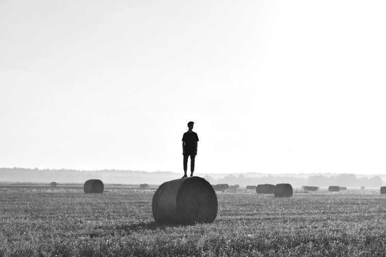 Full length of man standing on hay bale against sky