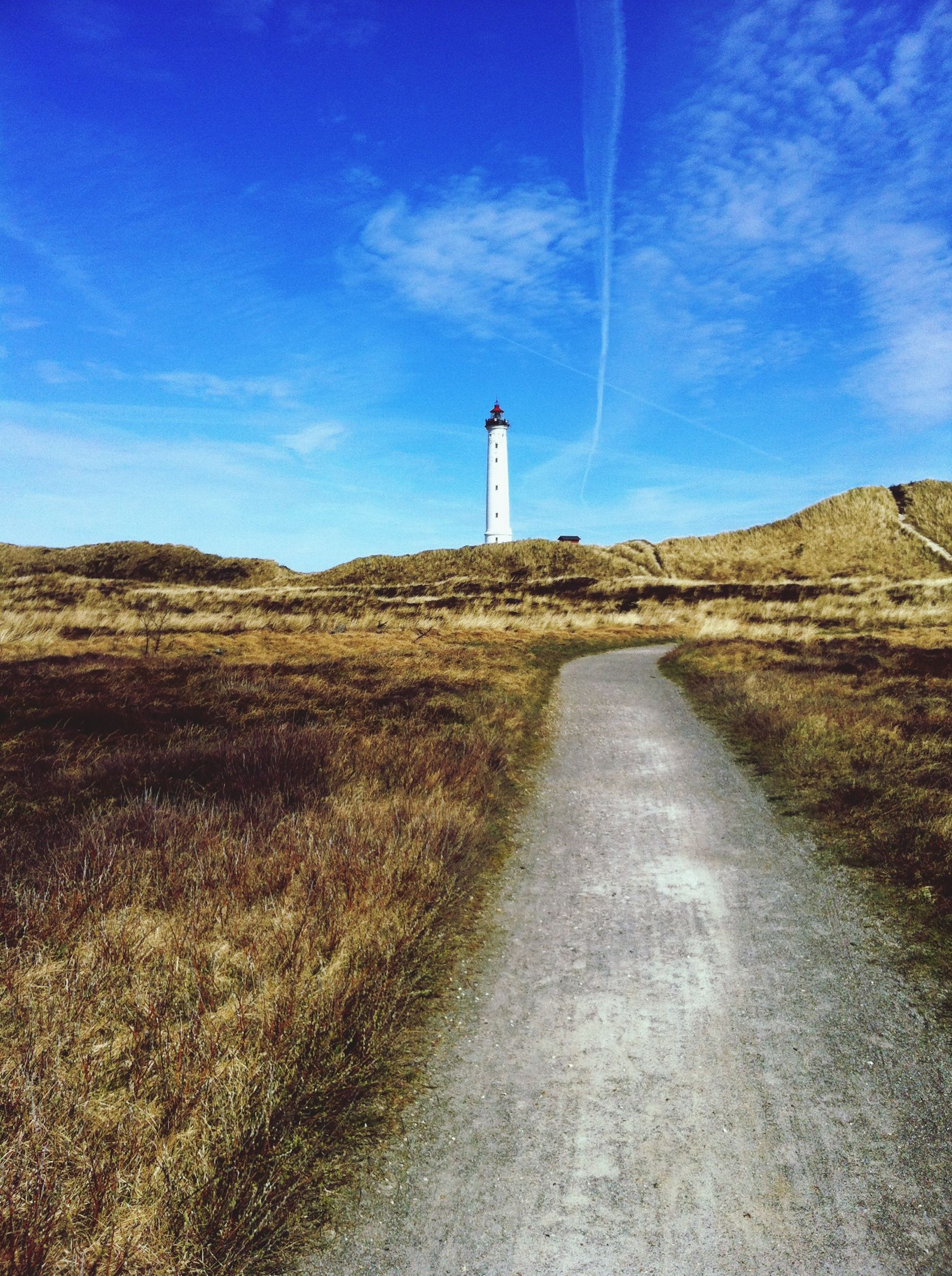 the way forward, guidance, sky, lighthouse, direction, built structure, landscape, tranquility, blue, grass, architecture, tranquil scene, building exterior, nature, day, cloud - sky, cloud, protection, leading, field