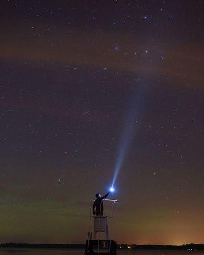 Man With Laser Light Toward Star Field