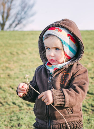 Toddler girl on dyke playing with stick– Hindeloopen, Netherlands, Europe Blue Eyes Exploring Grass Happiness Nature Caucasian Child Childhood Cute Front View Girl Holding Knit Hat One Person Outdoors Playing Portrait Rural Scene Serious Stick Talking Toddler  Toddlerlife Waist Up Warm Clothing