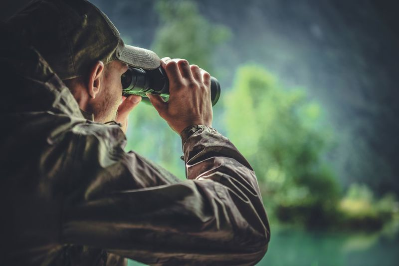 Man Looking Through Binoculars Against Tree