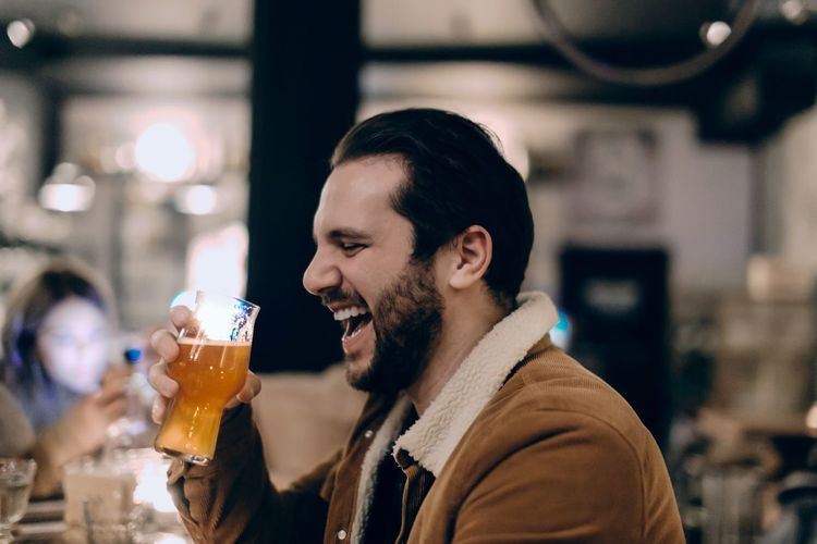 Portrait of a smiling young man drinking glass