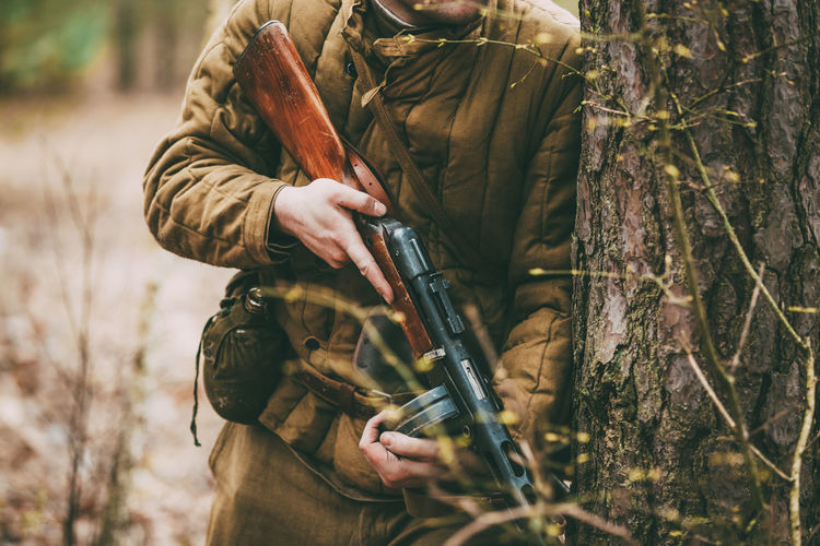 Unidentified re-enactor dressed as Russian Soviet soldier in camouflage in forest Re-enactors Tree Forest Weapon Gun Rifle Military Hunter Soviet Solder Camouflage Army Front Great Historic Victory War Ww2 WWII