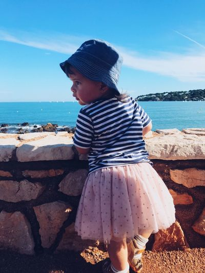 Rear view of girl looking away while standing by sea against sky
