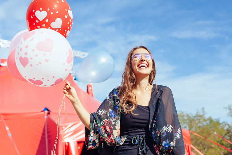 Low Angle View Of Cheerful Woman Holding Helium Balloon Against Sky