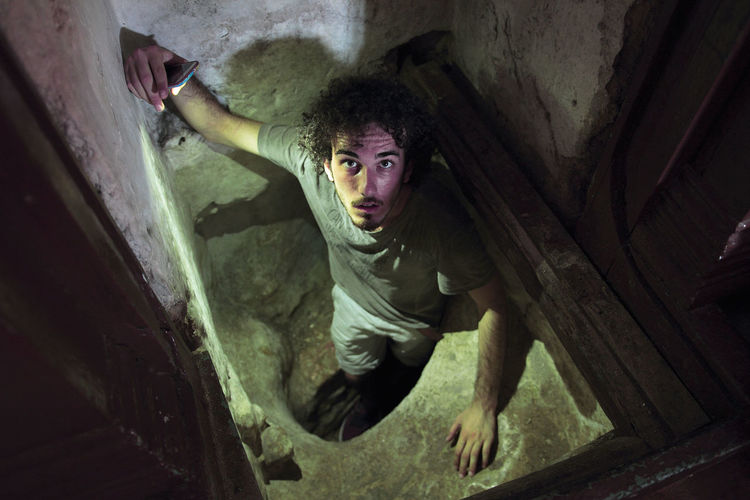 High angle view of young man exploring obsolete basement