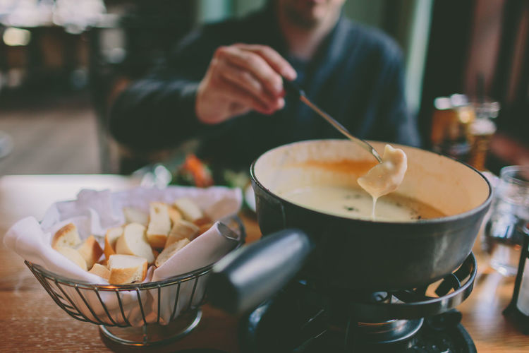 Man dipping bread into cheese fondue. Comfort Food Bowl Cheese Close-up Day Focus On Foreground Fondue Food Food And Drink Indoors  Preparation  Real People Table