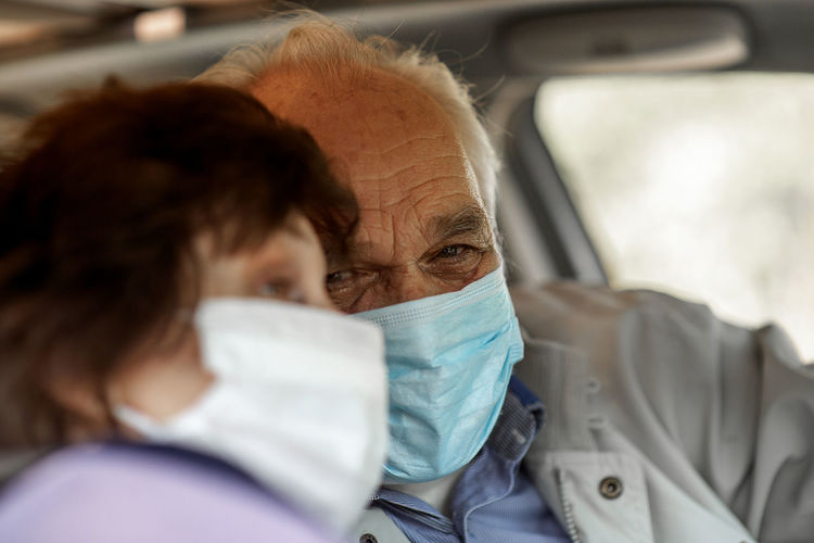 An elderly senior couple in medical face mask driving a car.  travel and old people concept