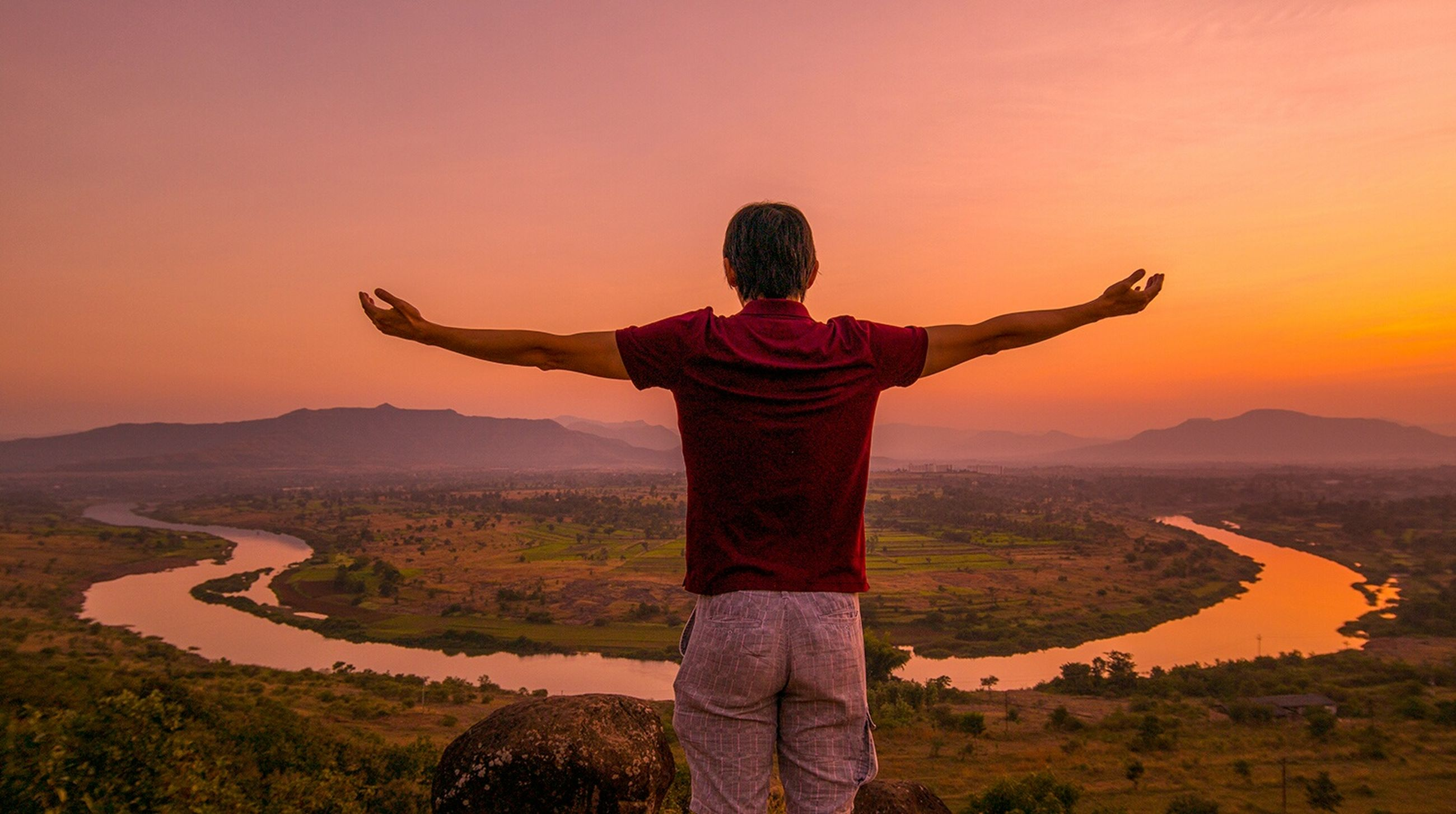 leisure activity, lifestyles, sunset, standing, landscape, casual clothing, sky, full length, three quarter length, mountain, tranquility, tranquil scene, arms outstretched, scenics, field, beauty in nature, nature, orange color
