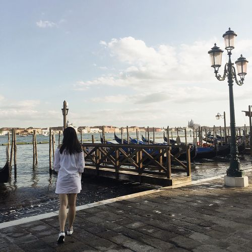 Rear view of woman walking on promenade by gondolas moored on grand canal