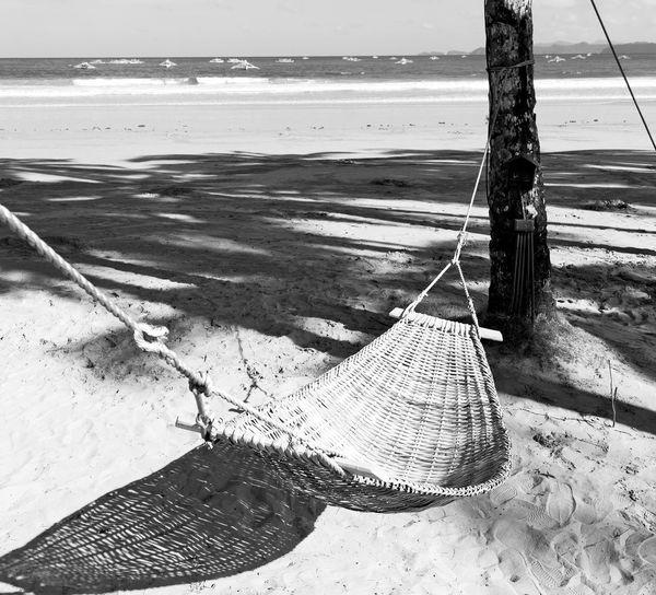 Fishing net on beach by sea against sky
