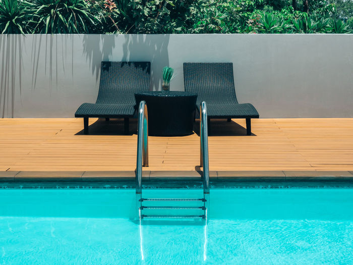 Empty chairs and tables in swimming pool